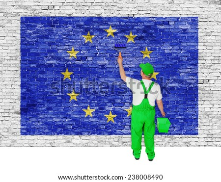 Painter covers white brick wall with flag of European Union - stock photo