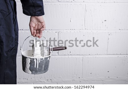 Painter / decorator holding paint bucket with brush in front of painted wall - stock photo