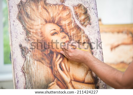 Painter drawing a wonderful picture with a great woman on it