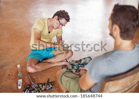 Painter drawing portrait of his client - stock photo