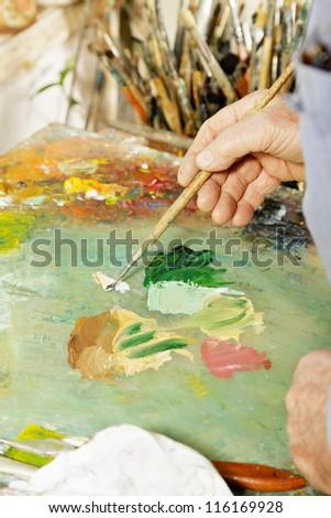 Painter hands mixing paints on palette - stock photo