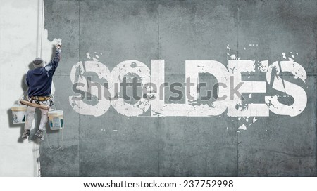 Painter hanging from harness painting a wall with the word sales in French - stock photo