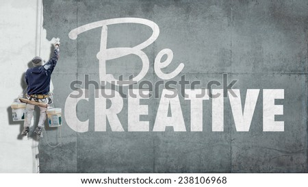 Painter hanging from harness painting a wall with the words be creative - stock photo