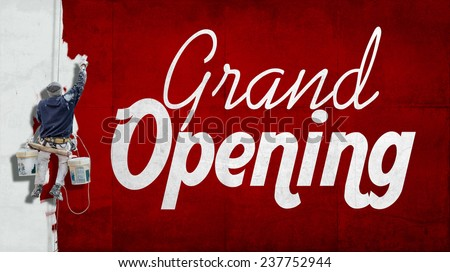 Painter hanging from harness painting a wall with the words Grand opening - stock photo