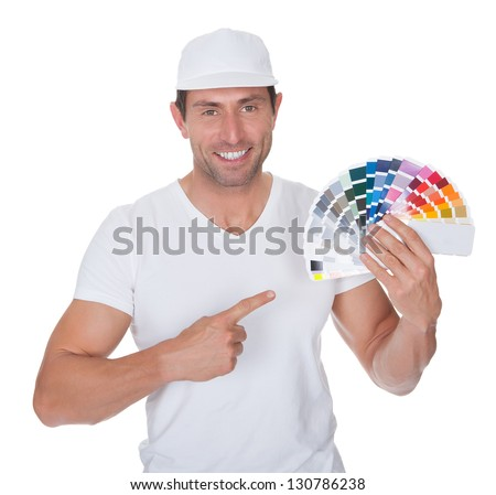 Painter Holding A Paint Roller And Spectrum Of Colour Samples On White Background - stock photo