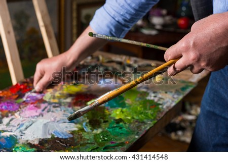 Painter holding professional paintbrushes and mixing paint by paletteknife on the colorful palette of blended oil paints in a gallery