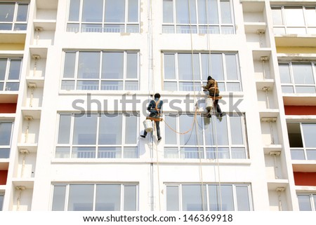 painter in high rise buildings, north china - stock photo