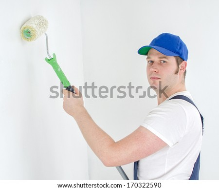 Painter in uniform paints the wall. - stock photo