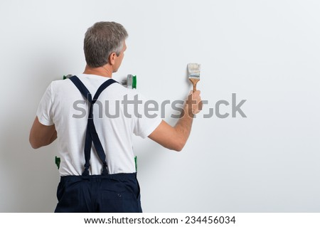 Painter On Stepladder Painting Wall With Brush - stock photo