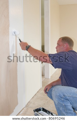 Painter painting dining room wall with roller brush - stock photo