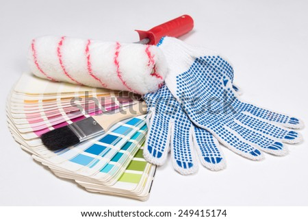 painter's tools - brushes, work gloves and colorful palette over white background - stock photo