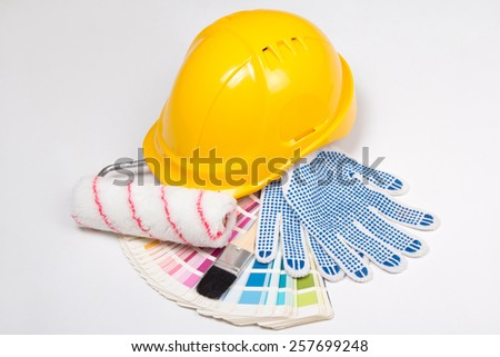 painter's tools - brushes, work gloves, helmet and colorful palette over white background - stock photo
