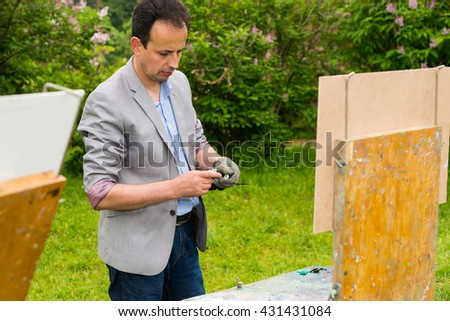 Painter Standing By His Sketchbook And Squeeze His Paint In The Garden - stock photo