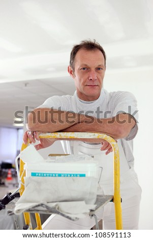 Painter stood at the top of step-ladder