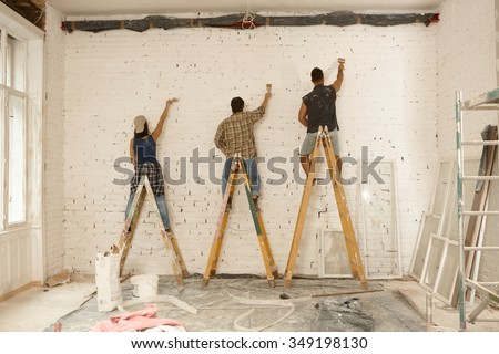 Painter team working on renovation site, standing on ladder, painting wall by brush.