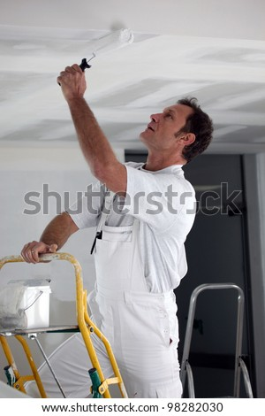 Painter using roller to coat ceiling - stock photo