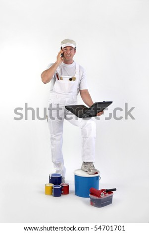 Painter with phoning in front of a laptop computer on white background - stock photo