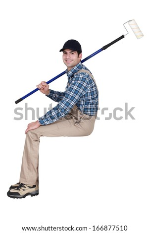 Painter with roller sitting on ledge - stock photo