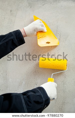 Painter with tools at workplace; hands of painter holding float and painting roller against the concrete wall