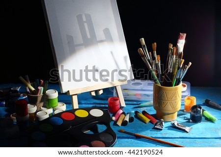painter workplace canvas, brushes and easel - stock photo