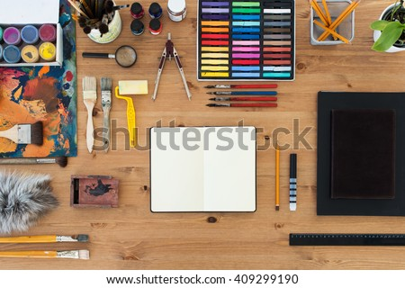 Painter workplace top view. Wooden table of an artist with art tools for drawing. - stock photo