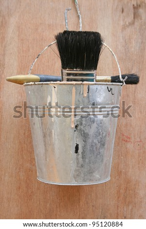 Painters bucket with brushes hanging on a hook.