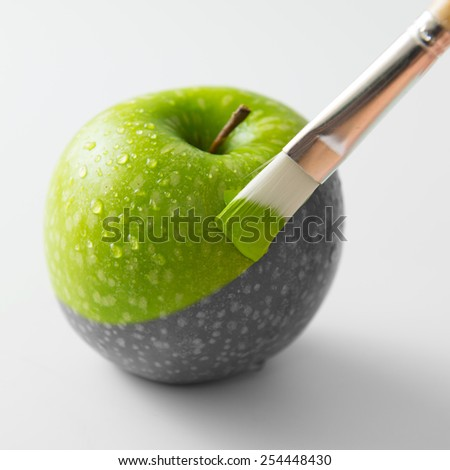 Painting a fresh green apple with paintbrush - stock photo