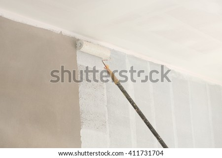 painting a wall and ceiling with paint roller