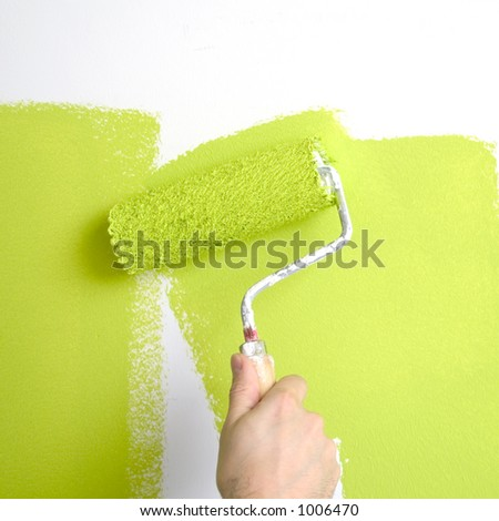 painting a wall with a roll - stock photo