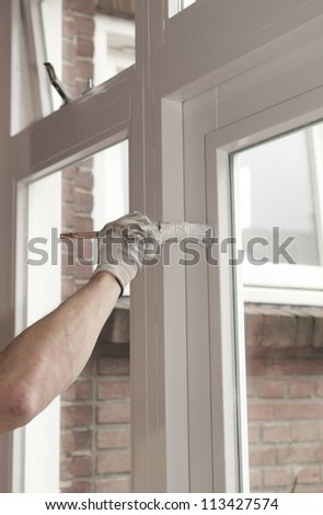 Painting a wooden window with white paint