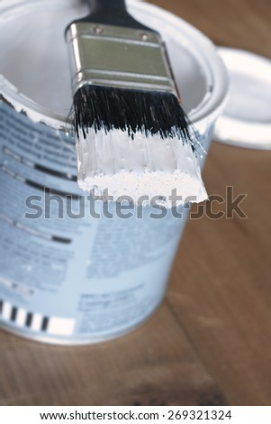 Painting and decorating shallow focus view of a pot of white paint and brush - stock photo
