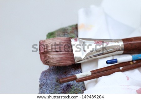 Painting brush with color on it and dirty towels  - stock photo