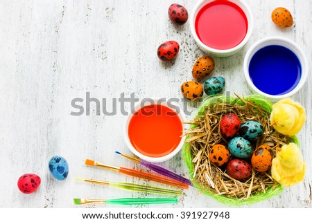 Painting easter eggs background. Paint brush colorful egg on white table. Handmade Easter crafts blank space for text top view - stock photo