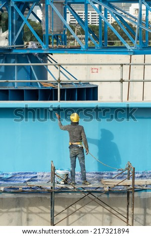"painting facade builder worker ""movement"" with roller at Water Treatment Plant - stock photo"