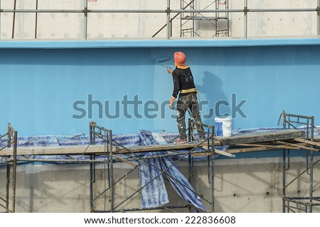 "painting facade builder worker ""movement"" ; with roller at Water Treatment Plant - stock photo"