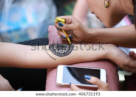 Painting Henna paste on woman's hand in the street. India, tattoo painting