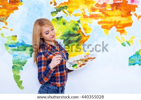 Painting is an expression of self. Portrait of an attractive young woman holding a brush and palette over wall painted like map of the world - stock photo