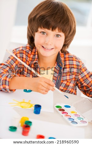 Painting is fun. Top view of little boy relaxing while painting with watercolors sitting at the table - stock photo