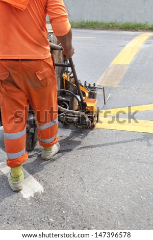 Painting machine and worker at road construction site - stock photo