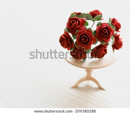 painting miniature red roses on a wooden table. beautiful small world - stock photo
