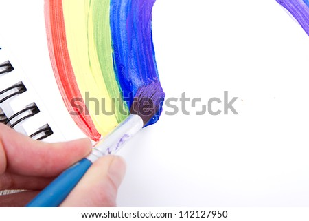 Painting of rainbow on notebook or sketch book with paintbrush, close-up - stock photo