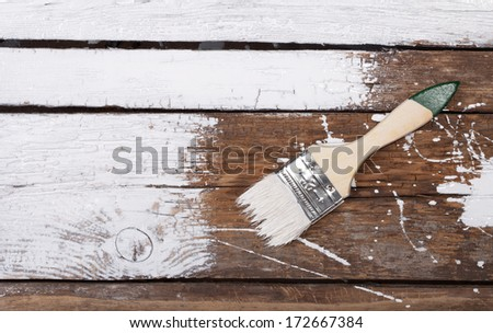 painting old wooden surface with white paint - stock photo