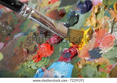Painting paintbrush on colorful painting palette. Shallow DOF. - stock photo