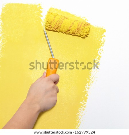 Painting roller on white wall with yellow paint - stock photo