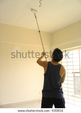 Painting the ceiling with a roller - stock photo
