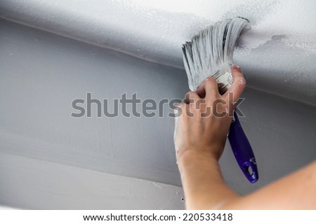 Painting the Edges of the Ceiling with Paintbrush - stock photo