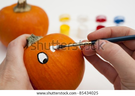 Painting the eyes on a pumpkin - stock photo