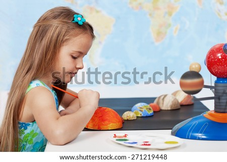 Painting the sun - elementary schoolgirl in science class learning about the solar system - stock photo