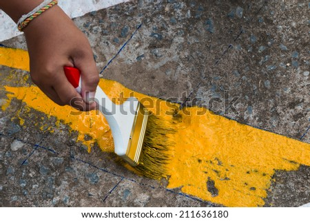 painting the the yellow line on the concrete road - stock photo