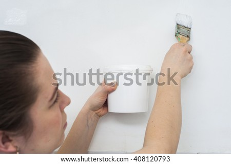 Painting the wall: paintbrush in female hands.